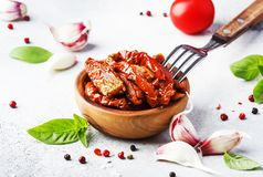 Sun dried tomatoes in olive oil with green basil and spices in wooden bowl on gray kitchen table, place for text royalty free stock photography