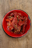 Sun-dried tomatoes with olive oil in red enamel Stock Photography