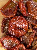Sun dried tomatoes with olive. Oil on wooden surface Stock Photography