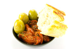 Sun Dried Tomatoes, Olives and Crusty Bread. Pile of red sun dried tomatoes with three green olives and crusty bread in a small black dish on a white background Stock Photography