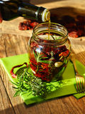 Sun dried tomatoes prepared as antipasti. Photo shows how to prepare sun dried tomatoes in a jar with native olive oill Stock Photos