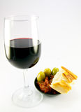 Sun Dried Tomatoes and Red Wine. Pile of red sun dried tomatoes with three green olives and crusty bread in a small black dish with a glass of red wine on a Royalty Free Stock Photography