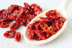 Sun dried tomatoes. Still life image - closeup of sun dried tomatoes on a wooden spoon and a heap in the background Stock Images