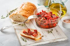 Sun dried tomatoes. In glass jar on white cutting board on light background Royalty Free Stock Photography