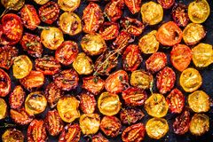 Sun-dried yellow and red cherry tomatoes with olive oil and thyme Royalty Free Stock Photography
