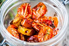 Sun-dried yellow and red cherry tomatoes with olive oil and thyme Stock Photos