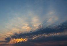 Sun durch Wolken von Grauem und von Orange ein Lichtstrahl Lizenzfreie Stockfotografie