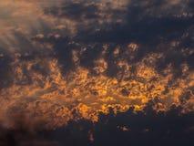 Sun durch Wolken von Grauem und von Orange ein Lichtstrahl Stockfotografie