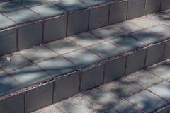 Sun e sombras em deteriorar etapas exteriores da telha imagem de stock