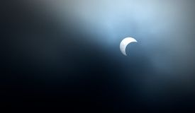 Sun Eclipsed by the moon. Moon eclipsing the sun May 20th, 2012. Clouds providing natural filter for lens Stock Photos