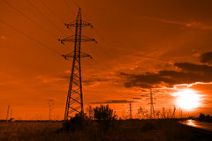 Sun and electricity - powerlines towers at sunset Stock Photo