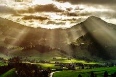 Sun emite la iluminación a través de las nubes y caer abajo al li Imagen de archivo