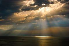 Sun emite a través de las nubes en el mar Imágenes de archivo libres de regalías