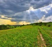 Sun emite a través de las nubes que flotan sobre el prado Imagen de archivo libre de regalías