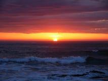 Sun en horizonte en la puesta del sol en la playa con el cielo anaranjado vivo hermoso fotografía de archivo