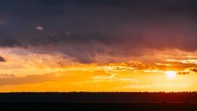 Sun en la puesta del sol en fondo del cielo sobre la tierra oscura Cielo dramático brillante con las nubes mullidas Time lapse de metrajes