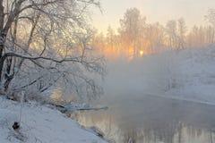 Sun&en x27; s rays i en frostig morgon på floden Fotografering för Bildbyråer