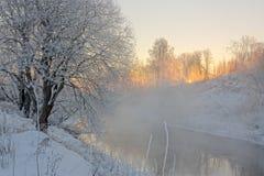 Sun&en x27; s rays i en frostig morgon på floden Arkivbild