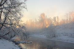 Sun&en x27; s rays i en frostig morgon på floden Royaltyfri Bild
