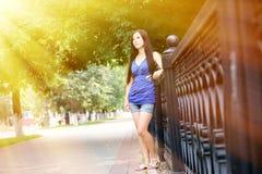 Sun&en x27; s-strålar faller på flickan lutade staketet Arkivbild