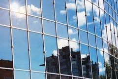 Sun enciende la reflexión de la nube del cielo en el edificio de oficinas de cristal Imagenes de archivo