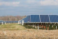 Sun energy collctors. Sun energy collector over plowed land and blue sky over Royalty Free Stock Photos