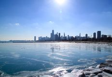Sun environ à placer au-dessus de l'horizon de Chicago et d'un lac Michigan congelé Photos libres de droits