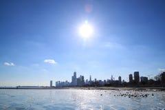 Sun environ à placer au-dessus de l'horizon de Chicago et d'un lac Michigan congelé Images libres de droits