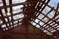Sun espreita através das árvores e do telhado do celeiro velho Foto de Stock