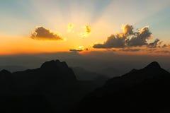 Sun está ajustando-se sobre a montanha Foto de Stock