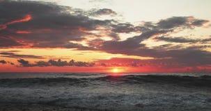 Sun est brillant au-dessus de l'horizon au crépuscule de coucher du soleil Ressacs de mer dans les lumières de ciel colorées de l banque de vidéos