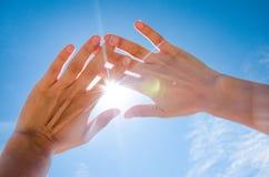 Sun est brillant par des doigts Photographie stock