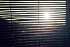 Sun est brillant par les abat-jour en bois Photos stock