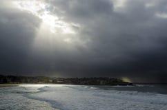 Sun estoura através das nuvens na praia de Bondi em Austrália Imagem de Stock Royalty Free