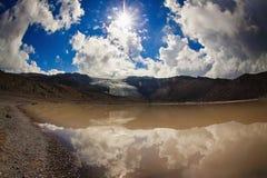 Sun et rayons de soleil hauts dans le ciel nuageux au-dessus du lac Photo libre de droits