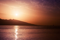 Sun, evening sky and sea water. Red toned Stock Images