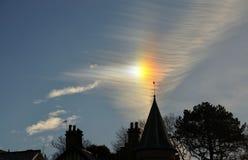 Sun förföljer och cirrusmolnet ovanför en kyrka. Royaltyfria Foton