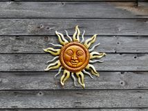 Sun face plaque on a wooden panel background