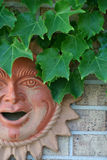 Sun Faced Man with Leaves 2. A terra cotta wallhanging of a sun faced man with leaves royalty free stock photo