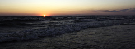 Sun falling into the ocean Royalty Free Stock Photography
