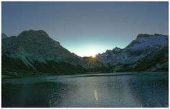 The sun falls behind the mountains stock images