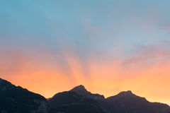 Sun fijó detrás de los picos de montaña en las montañas de Suiza Imagen de archivo