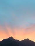 Sun fijó detrás de los picos de montaña en las montañas de Suiza Imagen de archivo libre de regalías