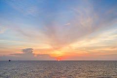 Sun fijó en el mar con el cielo azul y las nubes Foto de archivo libre de regalías