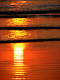 Sun Flame. The reflection of the setting sun on the beach looks like a bright inverted flame Royalty Free Stock Photo