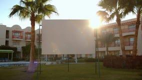 Sun flare behind a blank urban billboard stock video