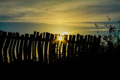 Sun flare and fence silhouette Stock Photography