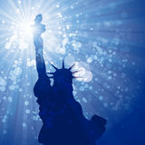 Sun flare liberty. Silhouette of statue of liberty against blue rays Royalty Free Stock Image