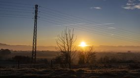 Sun flare shining over a blue dusk sky and foggy landscape stock photo