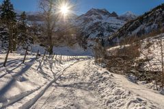 Sun flare and snowy trail in Gavarnie in the Pyrenees Stock Photos